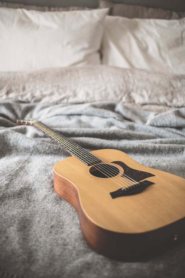photo of guitar on a bed